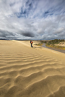 Man hikes along the Ahnewetut Creek which flows through the Great Sand Dunes in the Kobuk Valley National Park, Arctic, Alaska.