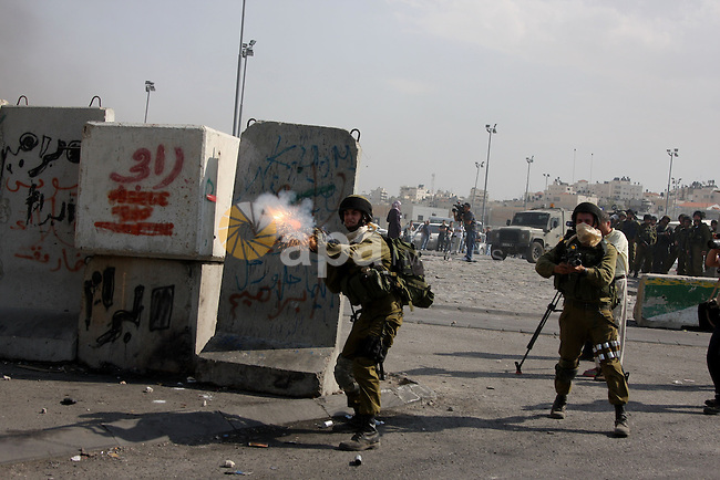 An Israeli soldier shoots tear gas on Palestinians stone throwers during clashes at the Kalandia checkpoint near the West Bank city of Ramallah October 9, 2009. Palestinian leaders on Thursday called for a one-day general strike and warned of more street protests over Jerusalem, where clashes at the flashpoint al-Aqsa mosque two weeks ago cranked up tensions in the disputed city. Israel is playing down Palestinian warnings that its security tactics risk a new Palestinian uprising. Photo by Issam Rimawi