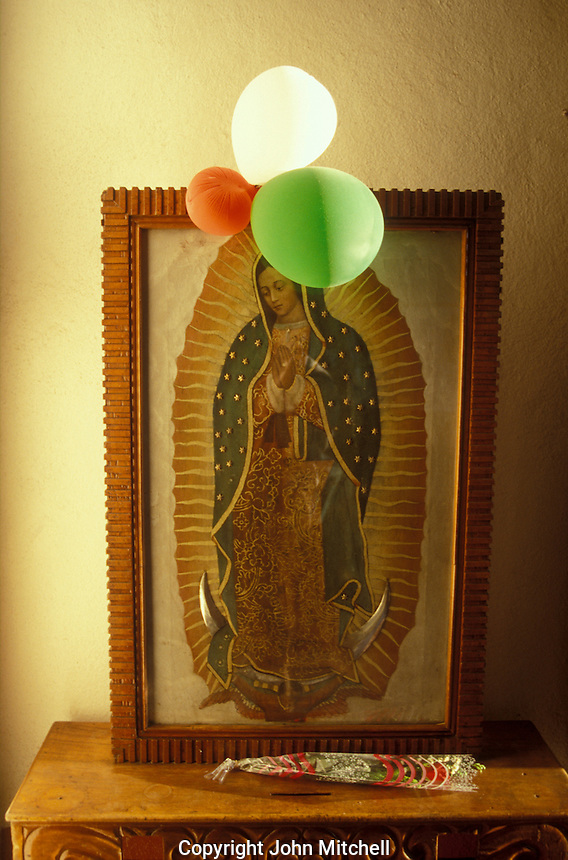 A portrait of the Virgin of Guadalupe decorated with red white and green balloons for the Dia de la Virgen de Guadalupe celebrations that are held every year on December 12, Patzcuaro, Michoacan, Mexico