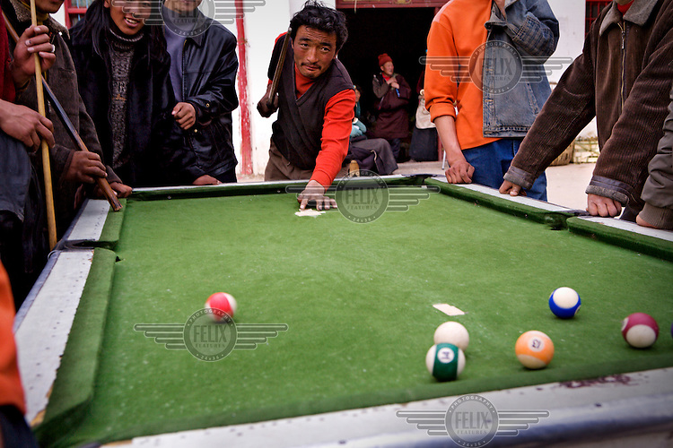 Men play a game of pool.