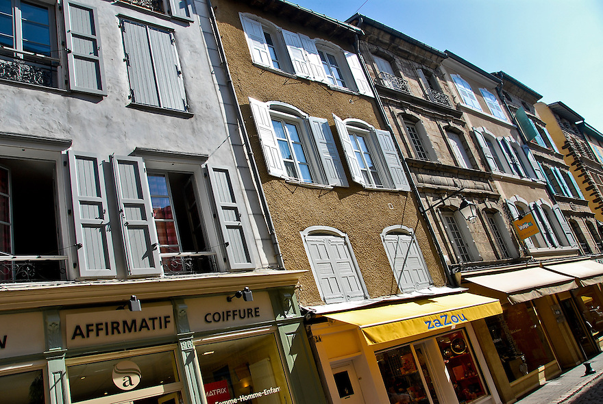 Windows open to the street in Le Puy-en-Velay, France.