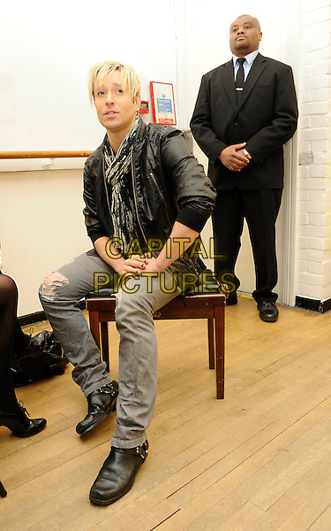 ANDREW STONE.The dancer from cult TV hit 'Pineapple Dance Studios' pictured at Pineapple Studios, London, England..March 10th, 2010.full sitting length black leather jacket scarf white grey gray jeans denim .CAP/FIN.©Steve Finn/Capital Pictures.