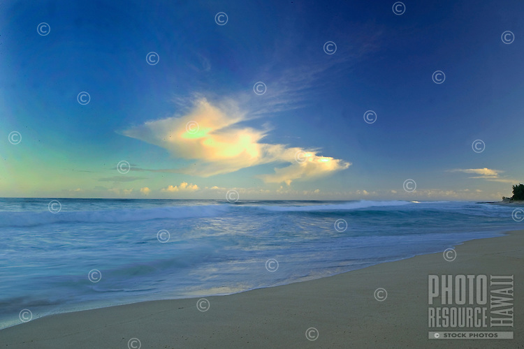 bright blue sky with clouds over a calm and glassy ocean and sandy beach