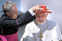 "George Gaenswein secretary of the Pope helps Pope Benedict XVI wear his ""saturno"" hat before the weekly general audience on June 16, 2010 in St Peter's square at the Vatican."