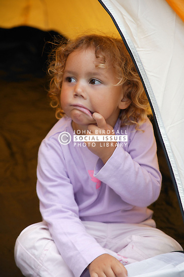 Young girl sitting in doorway of a tent in the garden; eating,
