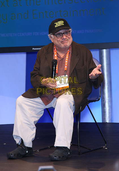 Danny Devito.Danny Devito makes an appearance at the Panasonic booth at the 2013 Consumer Electronics Show at the Las Vegas Convention Center, Las Vegas, NV., USA..January 9th, 2013.full length brown jacket baseball cap hat beige trousers chair sitting glasses hand arm.CAP/ADM/MJT.© MJT/AdMedia/Capital Pictures.