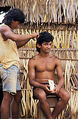 Ouro Verde, Brazil. Man giving another man a haircut outside a palm walled hut. Para State.