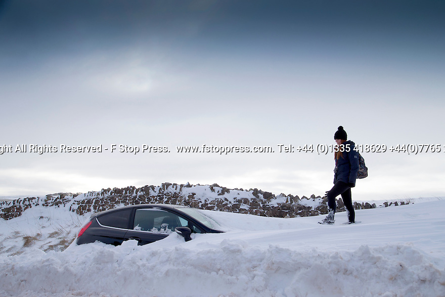 01/02/15<br /> <br /> After more overnight snow a walker climbs above a car buried in snowdrifts near Castleton in the Derbyshire Peak District.<br /> <br /> All Rights Reserved - F Stop Press.  www.fstoppress.com. Tel: +44 (0)1335 418629 +44(0)7765 242650