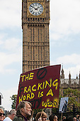 A protester holds a placard which says 'The Fracking World is a Dirty World' as he passes the tower of Big Ben during the Climate Change demonstration, London, 21st September 2014. © Sue Cunningham