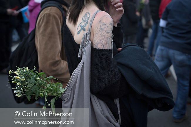 A woman with tattoos and a bunch of flowers pictured during a demonstration by the Alternative für Deutschland (AfD) political party in Berlin. Around 5000 supporters of the AfD took part in the march and rally through central Berlin calling on German Chancellor Angela Merkel to halt the influx of refugees into the country. Around one million refugees from the Middle East and north Africa arrived in Germany during 2015, 50,000 of whom came to Berlin.