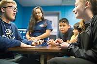 NWA Democrat-Gazette/CHARLIE KAIJO Ethan Campbell, youth development coordinator, (from left) Kayleigh Spoon, &Aacute;ngel Aguilar, Isaiah Tanchez and Summer Elder play cards, Monday, March 26, 2018 at the Boys and Girls Club of Rogers in Rogers. <br /> <br /> The new Boys and Girls Club of Rogers Teen Center opening across the street will feature a Cox technology center, a learning center where the kids can do homework, a big open game room with video games and table games like pool and  ping pong. <br /> <br /> &quot;Right now teens are in one small room here at the Rogers facility. Moving them over, we&rsquo;ll be able to serve more teens, offer more programming for teens and clear spots for the waitlist of this facility so they can serve more kids in this facility,&quot; said Caty Rogers, grants and data manager of the Boys and Girls Club.<br /> <br /> The old building will become strictly a youth facility with the new one focusing on teens. They&rsquo;ll also have soccer fields outside of that building which will be for youth and teen use. <br /> <br /> There is no set opening day yet, but they club is aiming to open the Teen Center's doors in May. They will get volunteers in the next month to help finish the project. <br /> <br /> &quot;There&rsquo;s not a lot of opportunities for teens in Rogers. We want to provide a space for teens that they enjoy going to and that&rsquo;s cool for teens,&quot; said Rogers. &quot;At the teen level you don&rsquo;t have to go to the club. Often times parents say you can stay home. We want it to be a place where teens want to be so ultimately we are a safe out of school time place.&quot; <br /> <br /> Additionally, Best Buy gave them funding for things like 3D printers, coding programs, photography and videography equipment.