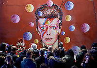UNITED KINGDOM, London : Crowds are gathered in front of a mural of British singer David Bowie, painted by Australian street artist James Cochran, aka Jimmy C, following the announcement of Bowie's death, in Brixton, south London, on January 11, 2016.