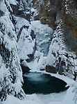Waterfall frozen in time flowing into the clear blue pool in Johnston Canyon in Canada