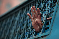Bangladesh's main opposition Bangladesh Nationalist Party (BNP) activist shows his hand from inside a police van after he was detained during a protest in Dhaka, Bangladesh.