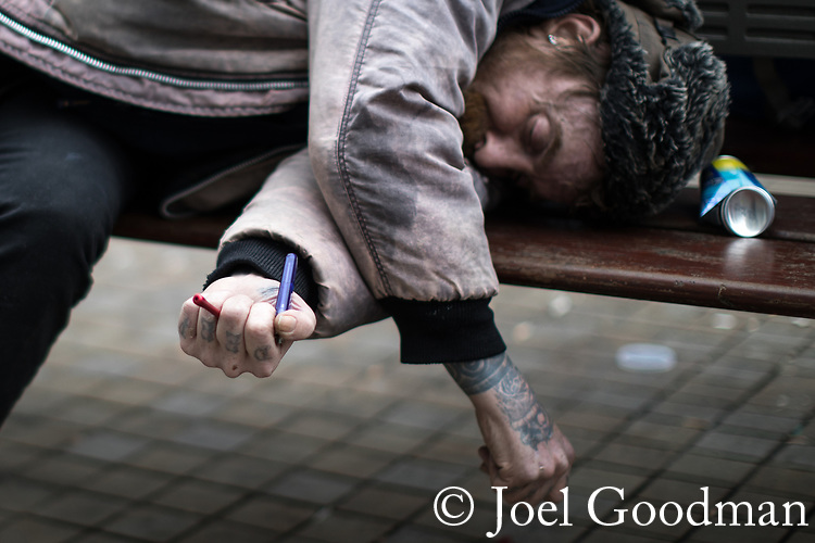 © Joel Goodman - 07973 332324 . 06/04/2017 . Manchester , UK . A man with a pipe in his hand lies slumped on a bench in front of Morrisons Supermarket in Piccadilly Gardens . An epidemic of abuse of the drug spice by some of Manchester's homeless population , in plain sight , is causing users to experience psychosis and a zombie-like state and is daily being witnessed in the Piccadilly Gardens area of Manchester , drawing large resource from paramedic services in the city centre . Photo credit : Joel Goodman