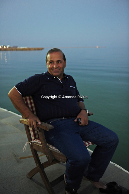 Ibrahim Ibrahimov sits down after dinner by the Caspian Sea with a Turkish business associate at the edge of his home between Sangachal and Sahil, Azerbaijan on August 16, 2012.