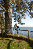 USA, California, Big Sur, Esalen, woman hops off of the fence near the Farm House with views of the Pacific in the distance, the Esalen Institute