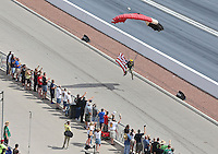 Apr. 7, 2013; Las Vegas, NV, USA: NHRA a sky diver brings in the flag opening the Summitracing.com Nationals at the Strip at Las Vegas Motor Speedway. Mandatory Credit: Mark J. Rebilas-