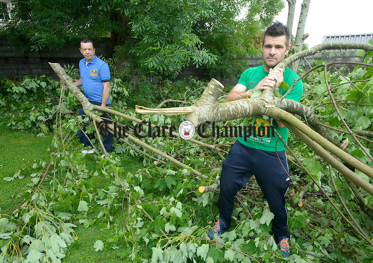 Ennis resident Martin Brennan and his son-in-law James Ferns with the trees which were vandalised in Martin's lawn early on Sunday morning June 12th.