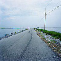 The single road that leads from the predominantly Native American community of Isle Jean Charles, Louisiana viewed toward the mainland. The road often floods and is in need of constant repair due to erosion. The island is clinging to life after decades of severe erosion of coastal marshes that once provided a buffer against hurricanes and high tides. Only 70 or so residents remain, down from 300 at its peak.