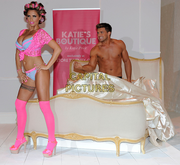 Katie Price (Jordan) & Leandro Penna.The launch photocall for Katie Price's new summer lingerie range for Store 21, The Worx, London, England..May 29th, 2012.full length pink lace top knotted bra cleavage belly stomach midriff knickers underwear tights stockings tattoo garter beige platform sandals shoes rollers curlers in hair side bed chest topless couple hands on hips fist hand arm funny .CAP/DH.©David Hitchens/Capital Pictures.