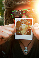 Dustin Fuller of Moscow, Idaho holds a Polaroid photo depicting the fur cap and green sunglasses he wore during the 2011 Bumbershoot music and arts festival in Seattle Center on Monday, September 5, 2011. Fuller said he purchased both the hat and the sunglasses at the festival.