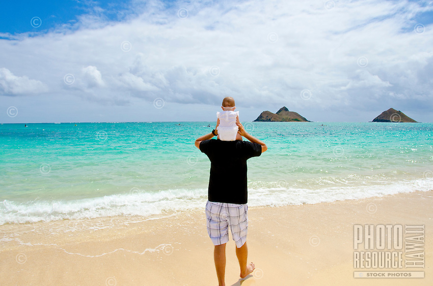 A father and daughter walking the shore of Lanikai Beach, O'ahu, with kayakers and the Mokulua Islands in the distance.