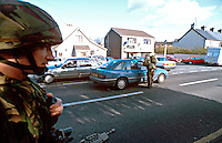 British Army soldiers on armed foot patrol on the streets of Northern Ireland. They are performing a moving vehicle check point stopping vehicles to check driving documents and to search for arms and explosives. This image may only be used to portray the subject in a positive manner..©shoutpictures.com..john@shoutpictures.com