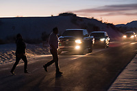 People begin to leave the park after the sun sets at White Sands National Monument near Alamogordo, New Mexico, USA, on Sat., Dec. 30, 2017. Park rangers work to clear out the park before the gates close soon after sun set.
