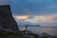 Female hiker stands below Møntind, Flakstadøy, Lofoten Islands, Norway
