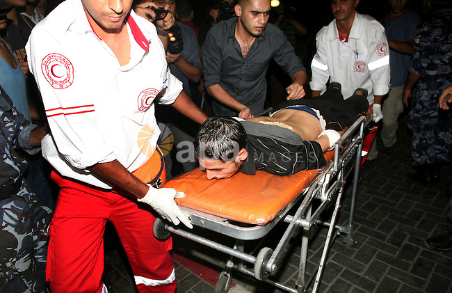A Palestinian man lies injured on a stretcher after being wounded in an Israeli air strike, at a hospital in Gaza City on August 19, 2011. Three Palestinians were killed -- one of them a five-year-old boy -- and three more wounded in an Israeli air strike in Gaza City late on August 19, medical officials said. The latest attack brought to 14 the number of Gazans killed since August 18 evening, when Israel began retaliating for the killing of eight of its citzens by suspected Islamic militants in the south of the country.   Photo by Mahmud Nassar
