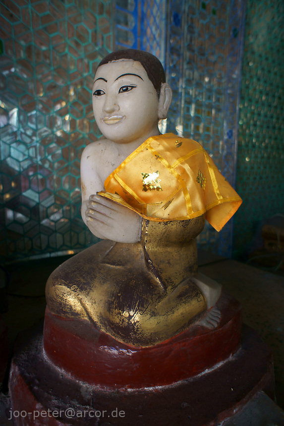 sculpture of a praying monk, worshipping Budda in a shrine of Shwedagon pagoda complex, Yangon, Myanmar, 2011