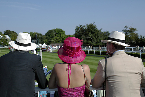 31 July 2004: Viewed from behind, three racegoers watching the horses in the Parade Ring at Goodwood Photo: Glyn Kirk/Action Plus...horse racing 040731