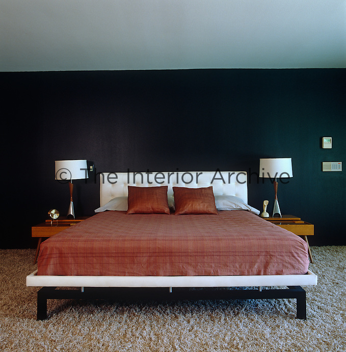The black wall in the master bedroom adds a sense of drama and is in stark contrast to the lamps and the white headboard