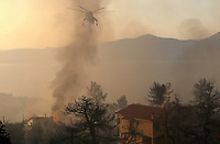 Pictured: A fire helicopter douses the flames near a house which is burning in the village of Kalamos.<br /> Re: A forest fire has been raging in the area of Kalamos, 20 miles east of Athens in Greece. There have been power cuts, country houses burned and children camps evacuated from the area.