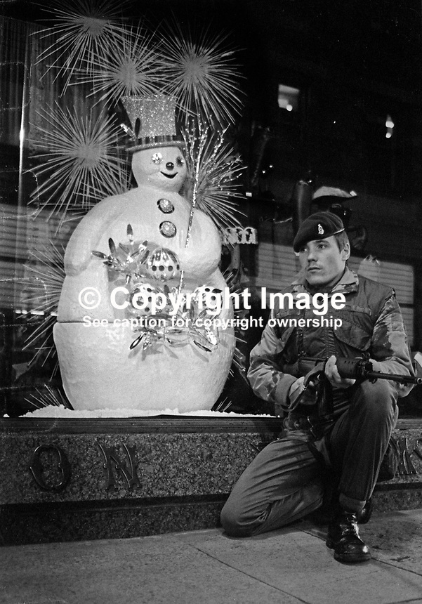 Christmas in Belfast, N Ireland, December, 1972. Soldier on security duty pauses beside a department store in the city centre. 197212010776<br /> <br /> Copyright Image from Victor Patterson, 54 Dorchester Park, Belfast, UK, BT9 6RJ<br /> <br /> t1: +44 28 9066 1296 (from Rep of Ireland 048 9066 1296)<br /> t2: +44 28 9002 2446 (from Rep of Ireland 048 9002 2446)<br /> m: +44 7802 353836<br /> <br /> e1: victorpatterson@me.com<br /> e2: victorpatterson@gmail.com<br /> <br /> The use of my copyright images is subject to my Terms &amp; Conditions.<br /> <br /> It is IMPORTANT that you familiarise yourself with them. They are available on my website at www.victorpatterson.com.<br /> <br /> None of my copyright images may be used on a website unless they are visibly watermarked, i.e. &copy; Victor Patterson within the body of the visible image. Metadata denoting my copyright must NOT be deleted. <br /> <br /> Web use is extra at currently recommended NUJ rates.