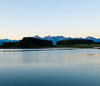 Forggensee lake at dawn with Allgäu Alps mountains rising in distance, Bavaira, Germany