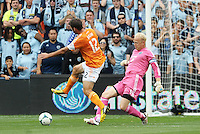 Jimmy  Nielsen goalkeeper Sporting KC clears the ball away from Will Bruin (12) forward Houston Dynamo ..Sporting Kansas City and Houston Dynamo played to a 1-1 tie at Sporting Park, Kansas City, Kansas.