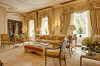 An opulent drawing room with an ornate gilded ceiling and floor to ceiling swagged curtains. The room is furnished in neutral and cream with antique furniture.