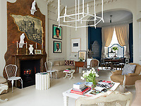 The living and dining rooms create an impressive, open space. A faux marble panel surrounds a real marble fireplace and an engraving of a Piranesi-style ruin is outlined in an irregular gilded frame whose shape echoes a Cocteau drawing. Resin falcons are painted white to mimic porcelain and a pair of Warholesque portraits by the artist Skid Stewart hang over a daybed.