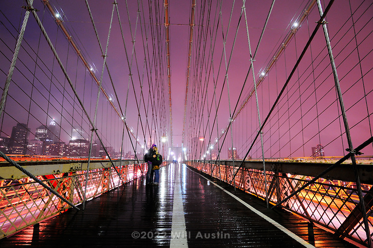 Couple kissing on the the Brooklyn Bridge.  Completed in 1883 and 1595.5 feet long, it is a National Historic Landmark that connects Manhattan and Brooklyn by spanning the East River.