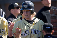 Willy Fox (9) of the Wake Forest Demon Deacons is congratulated by his teammates after scoring a run versus the Clemson Tigers during the second game of a double header at Gene Hooks Stadium in Winston-Salem, NC, Sunday, March 9, 2008.