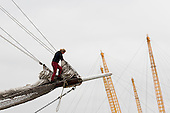 London, UK. 7 September 2014. A crew member stands on the bowsprit of the Loth Lorien as the ship passes the Millennium Dome. Tall ships travelling between Woolwich and Maritime Greenwich on the River Thames. The Royal Greenwich Tall Ships Festival 2014 will culminate with a Parade of Sail on the River Thames from Greenwich with fifty tall ships taking part. Photo: Bettina Strenske
