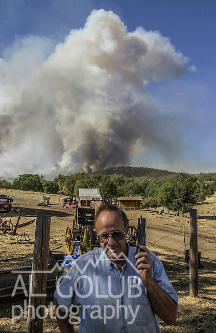 August 19, 2001 Coulterville, California  -- Creek Fire –  Alan Haigh listens to radio scanner while fire is blowing up on his ranch.  The Creek Fire burned 11,500 acres between Highway 49 and Priest-Coulterville Road a few miles north of Coulterville, California.
