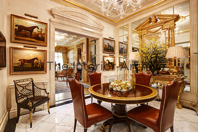 An opulent dining room with a mirrored wall and gilded cornice. The room is furnished with a round pedestal table and brown leather dining chairs.