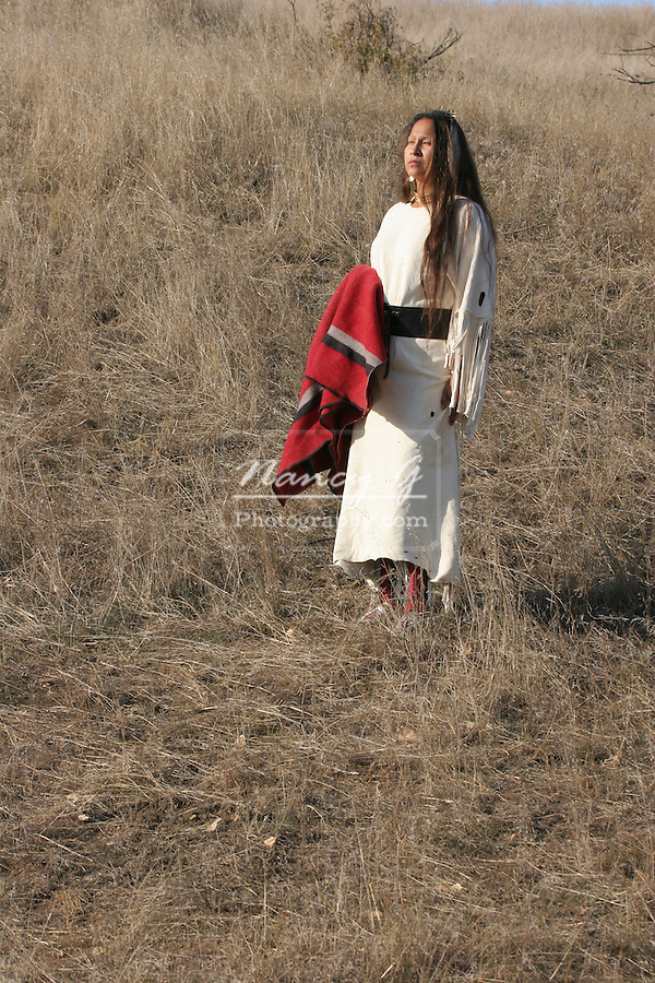 A Native American Indian woman standing with a red blanket in the prairie of South Dakota