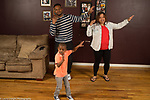 4 year old boy at home with parents doing dance with them following moves on a television (tv not visible)