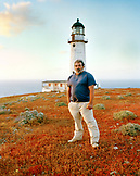 MEXICO, Baja, portrait of lighthouse keeper standing in front of lighthouse, San Benitos Islands