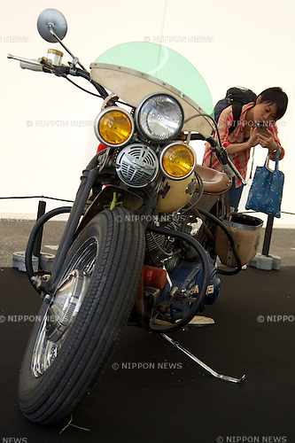 A visitor takes pictures of the motorcycle Harley Davidson at the Tokyo Motor Fes 2014 on October 11th in Odaiba, Tokyo, Japan. The Tokyo Motor Fes 2014 runs from October 11th to 13th with the aim of giving visitors of all ages a chance to interact with current and futuristic motorized vehicles. Held outside on reclaimed land in Tokyo Bay the event has enough space for visitors to test new vehicles and for a synchronized driving demonstration by the Cirque de Mobi. This year Mercedes-Benz and BMW will also participate along with 13 Japanese makers. (Photo by Rodrigo Reyes Marin/AFLO)