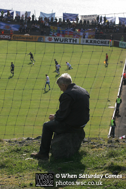 Faroe Islands 0 Scotland 2, 06/06/2007. Svangaskard, Toftir, Euro 2008 Qualifying. A Faroese man watching the action from the hillside outside the ground as the Faroe Islands take on Scotland in a Euro 2008 group B qualifying match at the Svangaskard stadium in Toftir. The visitors won the match by 2 goals to nil to stay in contention for a place at the European football championships which were to be held in Switzerland and Austria in the Summer of 2008. It was the first time Scotland had won in the Faroes, the previous two matches ended in draws. Photo by Colin McPherson.